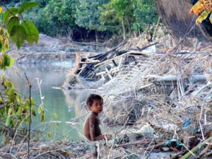 A child sits amid remains of a collapsed house near Brahmaputra river after flood waters entered Rekhachapori Village in Silapothar, Assam on Thursday (Image by Press Trust of India)