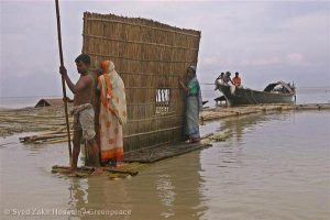 People affected by flooding of the Jamuna River dismantle their homes and move to higher grounds