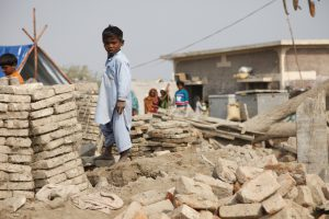 A child stands amongst the remains of buildings destroyed by the recent flooding in Sindh province, Pakistan (Photo: DFID)