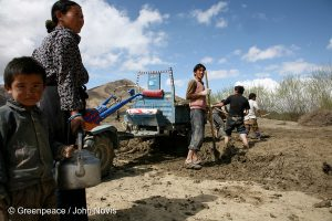 A woman brings tea to local men who shovel mud to make building bricks in Tibet