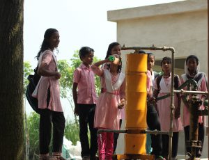 Schoolchildren in West Bengal drink water from an Amrit drinking water purification system connected to a hand pump [image by Indian Institute of Technology Madras]