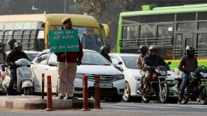 """A policeman holding a sign that reads, """"make it a pollution free city, enjoy your new year"""" [image courtesy Delhi government]"""