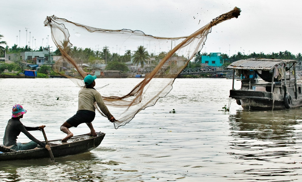 Traditional fishing in the Mekong delta: two men throw a fishing net into the Mekong Delta (Photo: Uwe R. Zimmer)