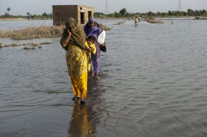 Pakistan's water crisis - Two women and a child walking through floods due to climate change