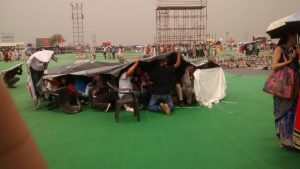 Around 50 media people huddled under a tarp to ward off hail [image by Juhi Chaudhary]