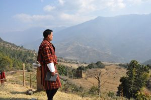 A local representative inspects fallow fields in the town of Phangyul, Bhutan [image by Dawa Gyelmo]