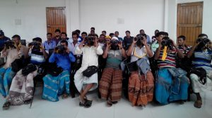 Fishermen being trained on using binoculars to spot dolphins [Image by WCS Bangladesh Program]