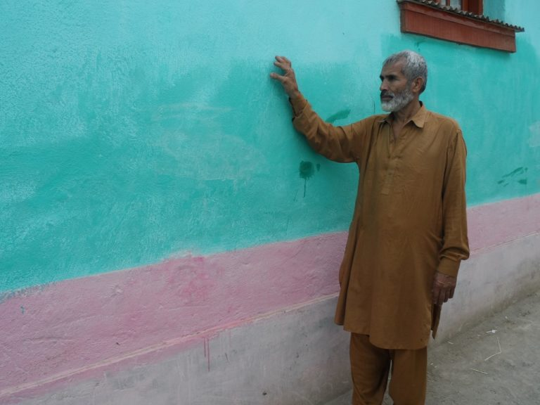 Saleem Khan shows exterior of a straw bale wall that is rendered with earthen plaster stucco [image by Aamir Saeed]
