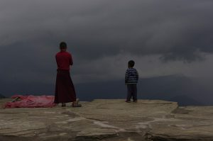 A monk and child stare at an approaching storm at Sanga Choling monastery in Sikkim, India [image by Andrea Kirkby]