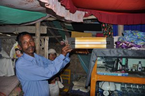A villager demonstrates a solar powered light in Mongla, Khulna, Bangladesh [image by Marufish/Flickr]