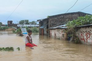 A woman contemplates her flooded home [image by: Munna Saraff]