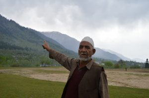 A Kashmiri man near a Budgam forest shows the degradation caused to forests over the past few decades [image by:  Athar Parvaiz]