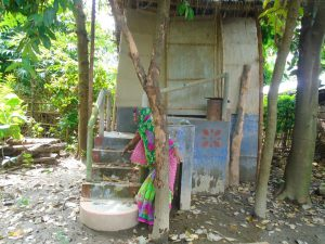 A woman indicates the last flood water levels that inundated the Kairi village. The toilet was still accessible [image by: Aparna Unni]