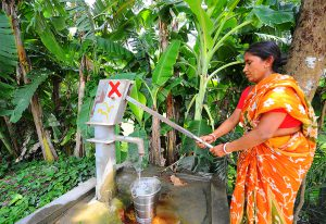 A woman pumps up water from a tubewell in West Bengal despite the red cross that signifies that there is an unacceptable level of arsenic in the water [image by Dilip Banerjee]
