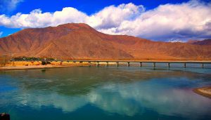 A bridge over the Yarlung Zangbo/Yarlung Tsangpo river west of Lhasa. The river later flows into India where it is known as the Brahmaputra [image by Eric/Flickr]