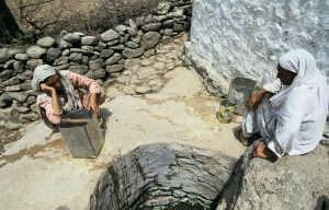 People sitting near a well collecting water in Pakistan. Image source: World Bank Photo collection.