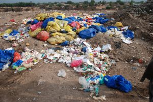 Trash, including hospital waste, is lying in the open in Aftab Abad where dwellers have forcibly stopped WSSP from dumping of solid waste due to proximity of the site with population [image by: Adeel Saeed]