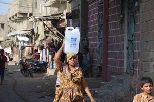 karachi slum during heatwave - woman carried bottle of water over her head