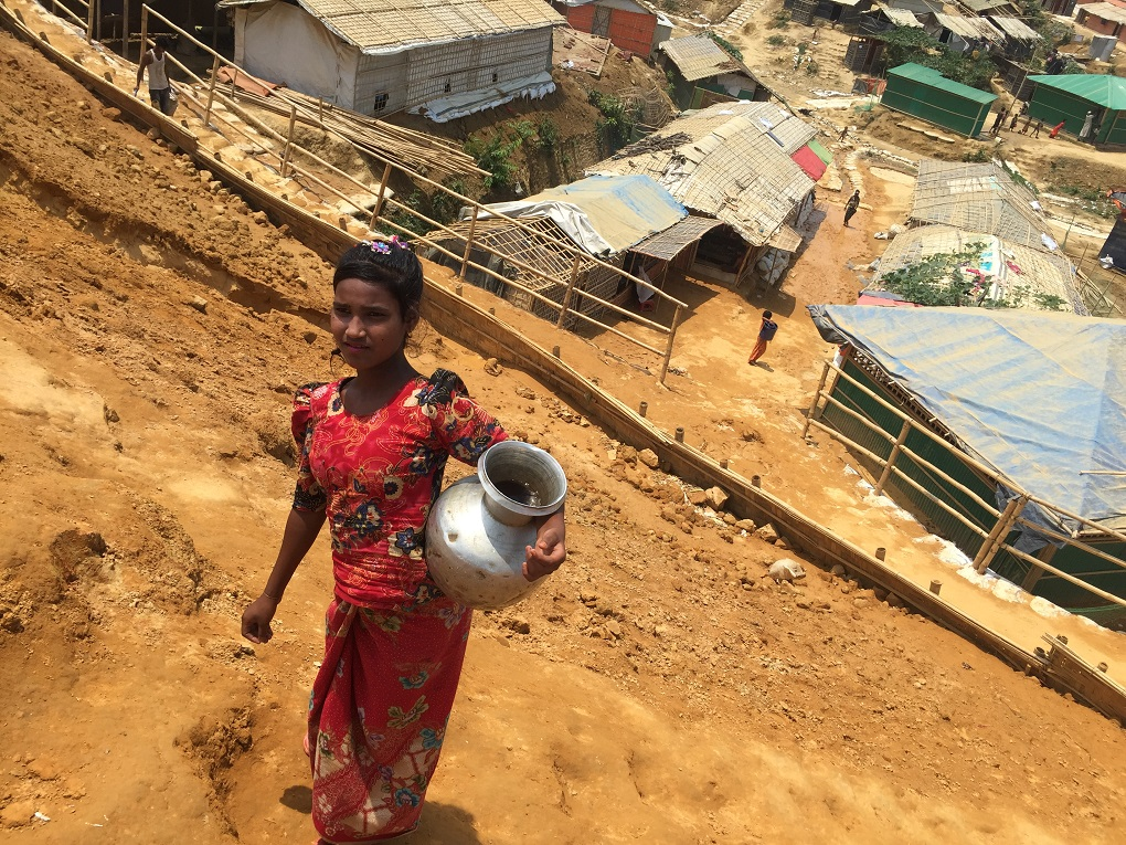 A Rohingya child was carrying water through a pitcher from a  tubewell far from her home [image by: Mohammad Al-Masum Molla]