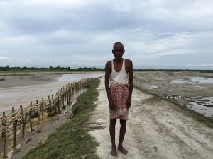 A resident of Raghunathpur standing on an embankment with bamboo revetment on the Sundari river [image by: Peter Gill]