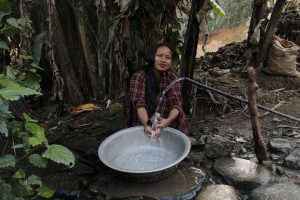 Sharada Bogati of Bidur-9 cleaning dishes beside her home. Unlike many neighbourhoods in Bidur, families in her neighbourhood get enough water for their daily use and also for vegetable farming [image by: Bhrikuti Rai]