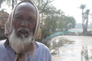 In a village on the edge of the Sundarbans and facing the Bay of Bengal, Jasimuddin Sarkar in front of his farm that now grows nothing, thanks to sea level rise, and his house that gets flooded with dirty saline water every third or fourth day [image by: Joydeep Gupta]