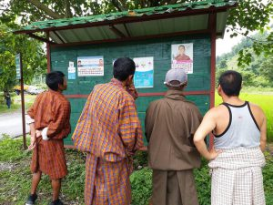 Bhutanese scrutinise claims on an election board - the only place where political parties are allowed to put promotional material [image courtesy: Kuensel]