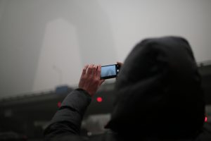Beijing resident takes a picture of the China Central Television Headquarters vanishing in the smog in Beijing [image by: Yat Yin / Greenpeace]