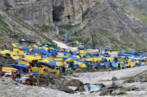 The Amarnath cave and the market near the shrine. Besides the market, there is a large langar (food canteen) which provides food to the pilgrims during the day; and dinner for those who stay at the site for the night [image by: Athar Parvaiz]