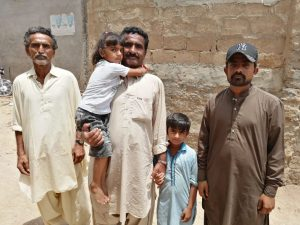 Nazeer Mirbaher (centre) is one of the half million people who have had to flee homes drowned by encroaching sea water [image by: Shahid Shah]