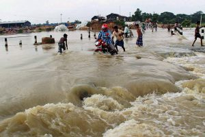 Villagers in Norjai Setu in Burdwan district of West Bengal try and navigate the flooded road [image by: Press Trust of India]