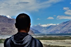 A local in the Nubra Valley of Ladakh, looking towards the Korakoram mountain range, which hosts the Siachen Glacier [image by: Athar Parvaiz]