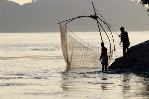Fishermen on the Brahmaputra, a river that winds through four countries [image by: Sumit Vij]