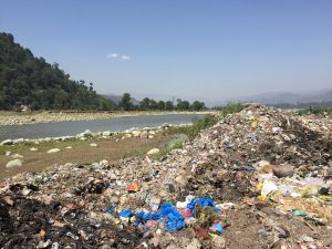 Much of the solid waste generated by municipal bodies is casually dumped in water bodies such as the Poonch river [image by: Raja Muzaffar Bhat]