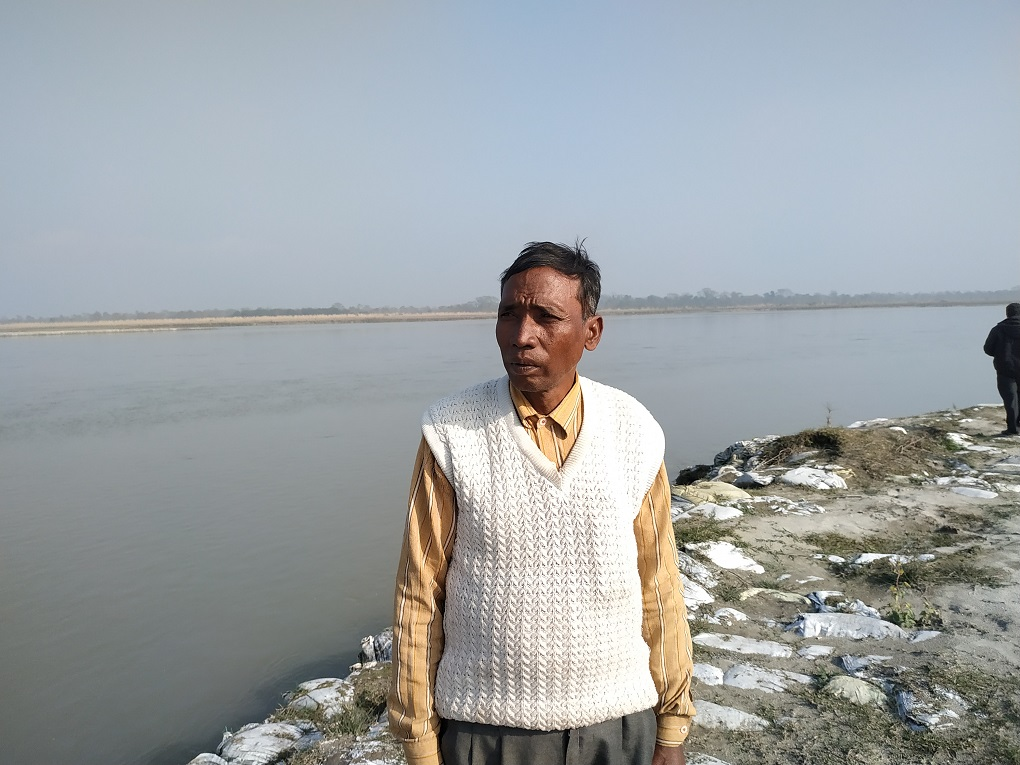 """Narayan Chaudhary, points out, """"The government settled us here, but the problem of soil erosion due to the river is now ruining everything."""" [image by: Manoj Singh]"""