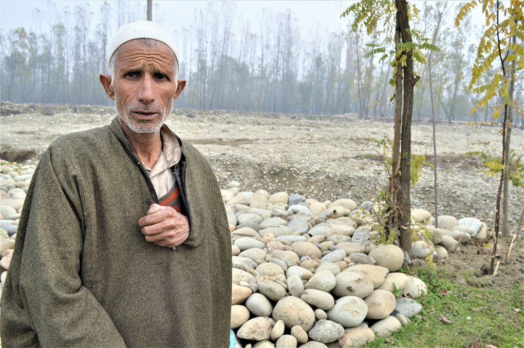 A man standing on the bank of a tributary of Jhelum in south Kashmir, Vishu. In autumn and winters, Jhelum's tributaries have extremely low flows [image by: Athar Parvaiz]