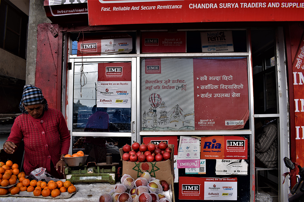A woman runs a fruit stall in front of an advertisement for a remittance delivery firm along banks of Mahakali