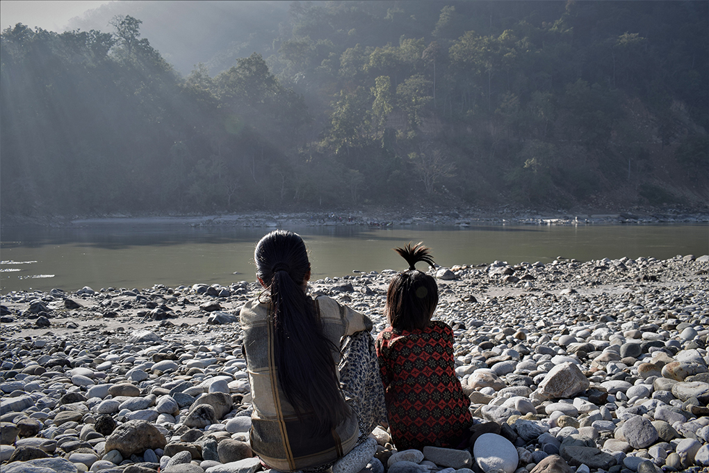 Two girls look across the Mahakali at India