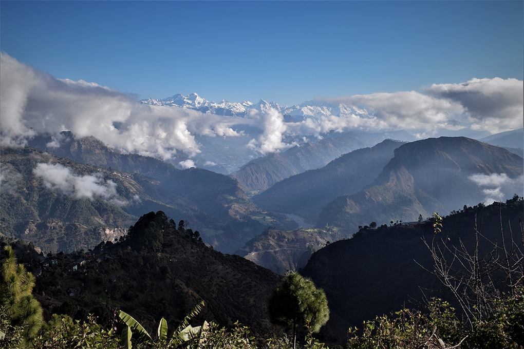 The snowclad Api Himal range of the High Himalayas in the background, with the Mahakali River flowing through richly forested mountains - as seen from the mountains of Dadeldhura, Nepal