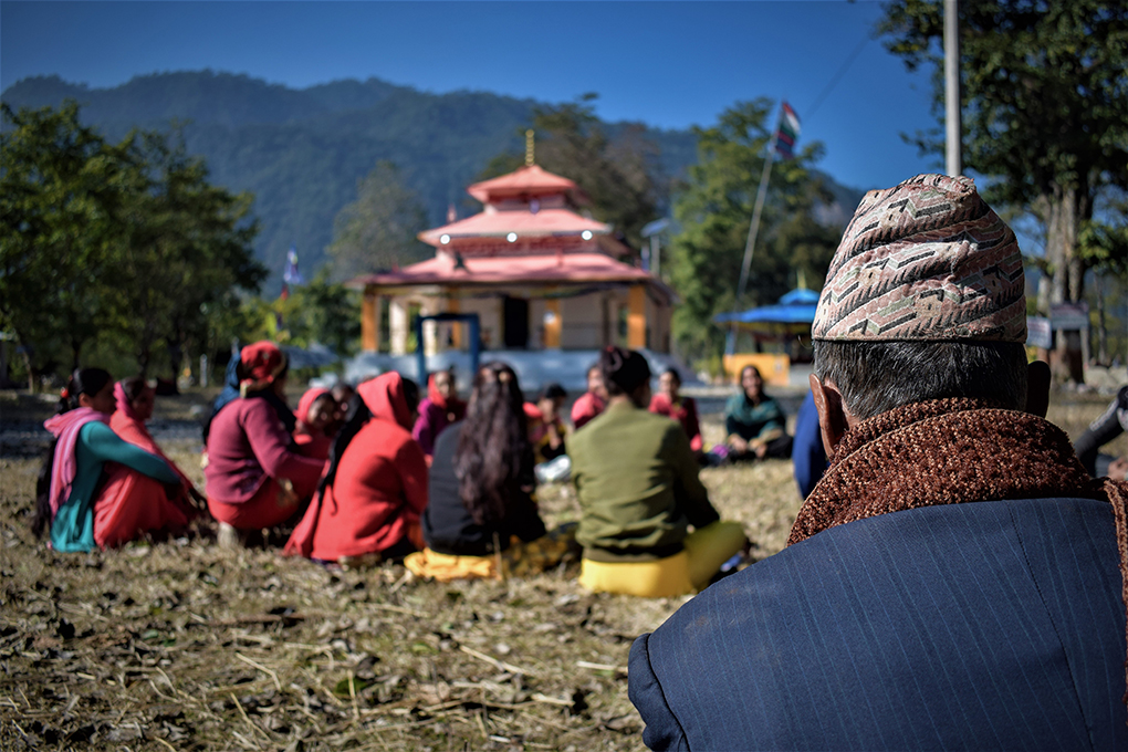 A WEC meets on the grounds of the village temple, while a man looks on