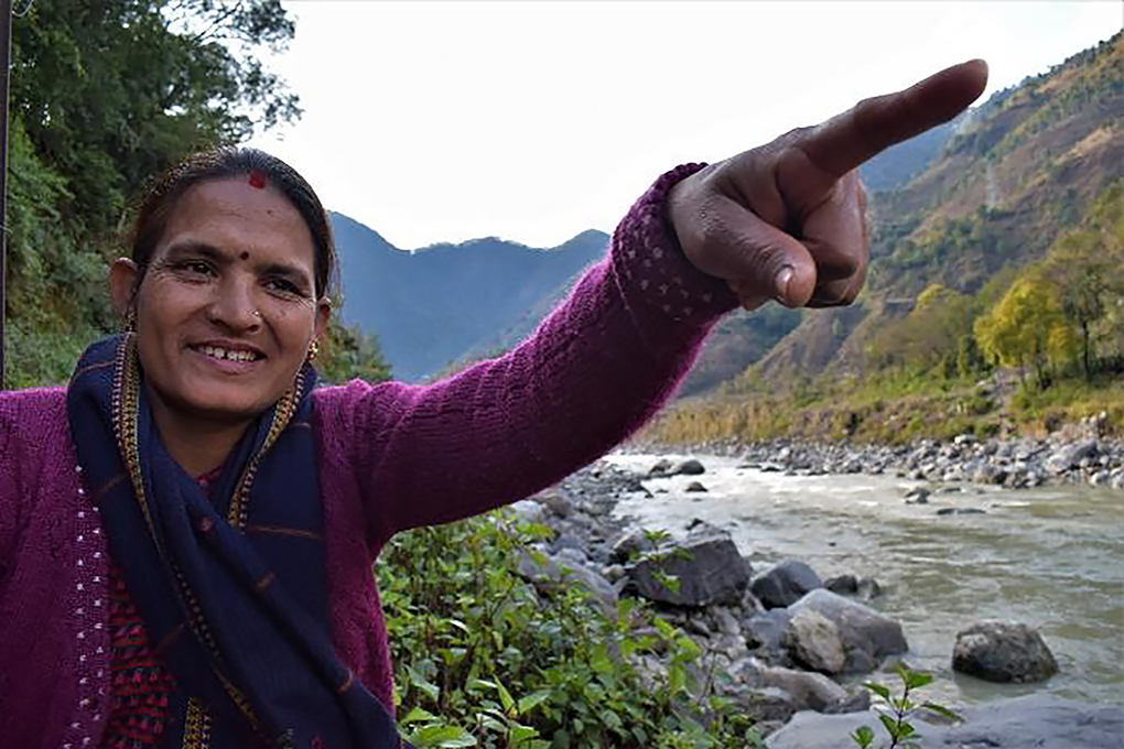 Woman points into the distance on the way to the Women's Empowerment Centre meeting near a village on the transboundary Mahakali River basin [All images by Minket Lepcha]