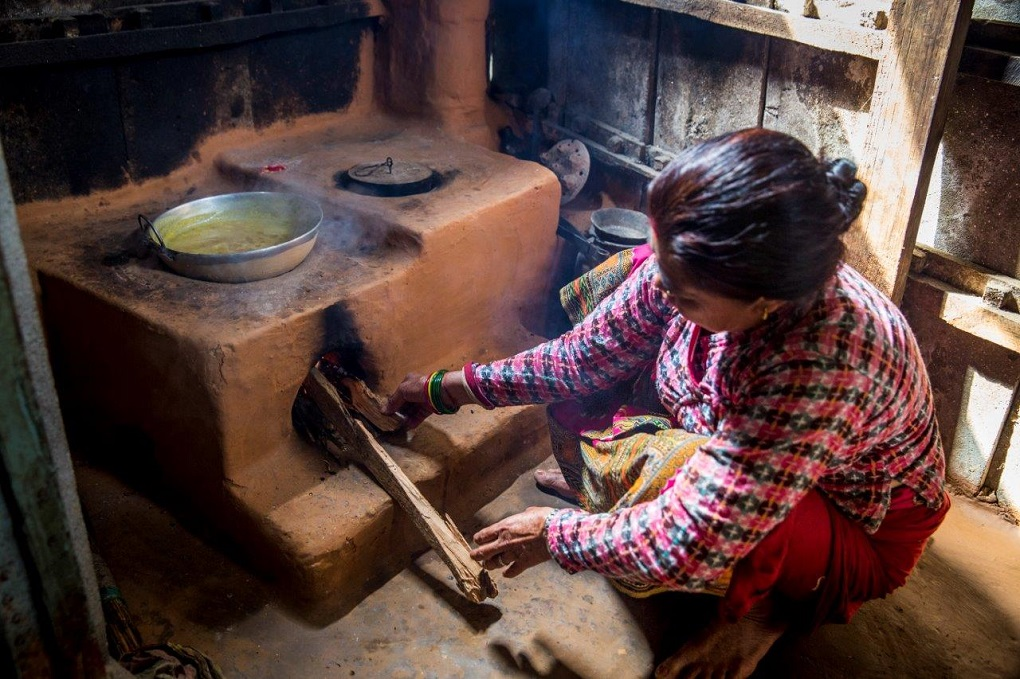 Woman burning cooking food using burning wood.  For many women in the HKH region the only form of energy is burning wood or biomass [image courtesy: ICIMOD]