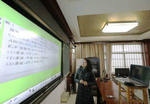 a teacher in south china delivers a lesson to an empty classroom virtually. Students remain isolated at home as part of efforts to prevent the spread of coronavirus