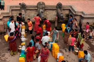 People stand for hours to fill their buckets and plastic containers from the ancient stone spouts or hitis in Patan, Nepal. (Majority World CIC / Alamy)