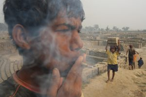 Clild labour in South Asia, sucheta Das. child smokes whilst boy carries building materials behind him