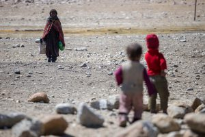 two children waiting for woman returning from collecting water in Ladakh
