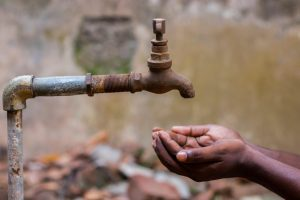 hands cupped to collect water from a tap in India's water crisis