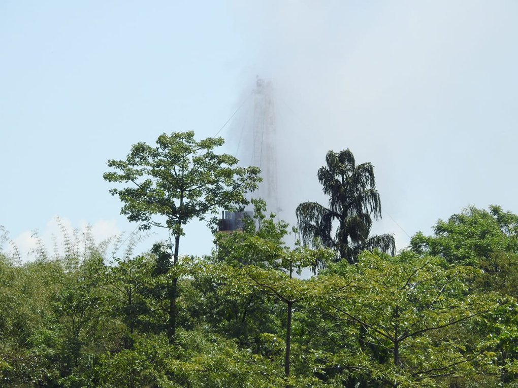 The rig spewing out gas through some trees, three days after the blowout [image by: Binanda Hatibaruah]