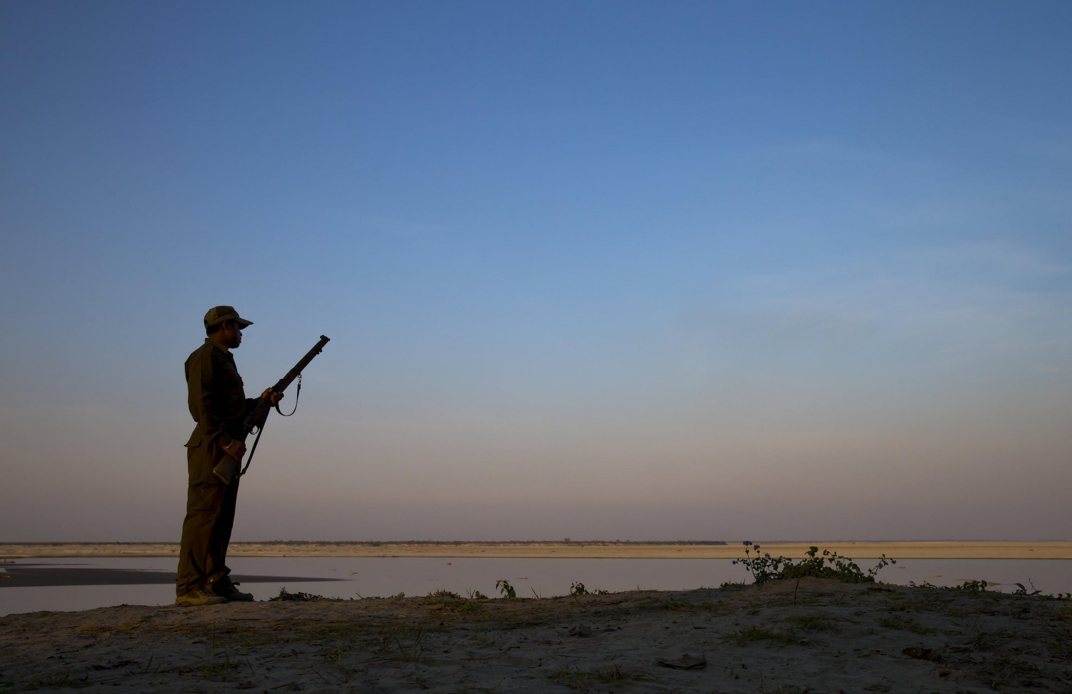 Forest guard armed with rifle, looking out over Brahmaputra River, Kaziranga N.P., Assam, India, January