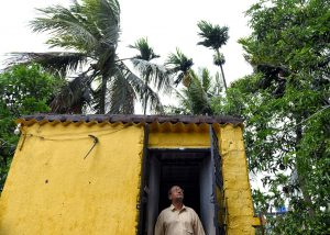 A man is seen looking up at the sky from his doorway before the hit of the Cyclone Amphan.Super Cyclone Amphan hits West Bengal with a speed of 130 kmph on the afternoon of 20th May [image: Alamy]